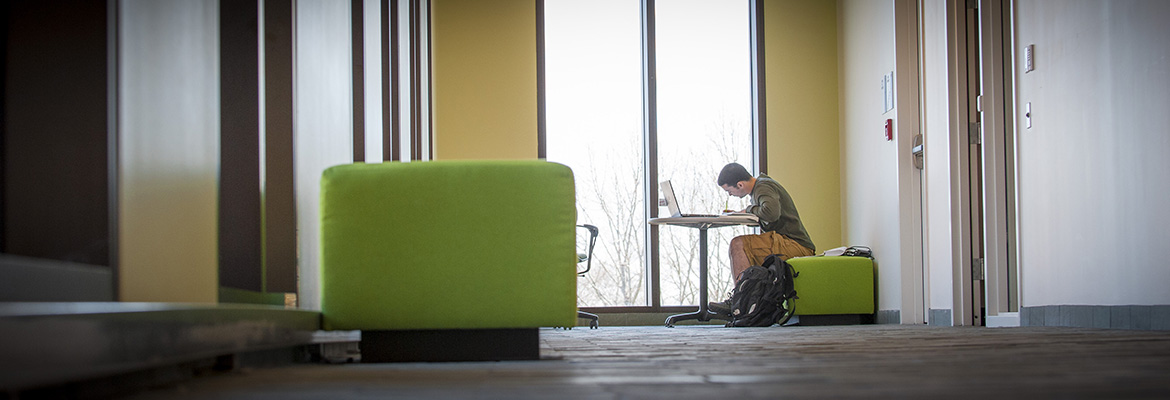 Young man studies over a laptop in Oak Hall